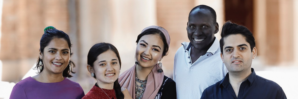 Five people of different ethnicities smiling with Year of Welcome logo